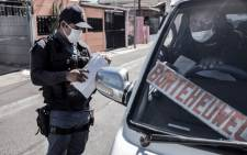 FILE: A South African Police Service (SAPS) officer checks the permit of a taxi driver in the Cape Flats area of Cape Town, on 30 March 2020. Picture: AFP