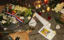 Flowers, candles and a picture of the front page of an edition of Charlie Hebdo are layed on the pavement near the offices of French satirical weekly Charlie Hebdo in Paris on 7 January, 2015, after armed gunmen stormed the offices leaving 12 dead. Picture: AFP.