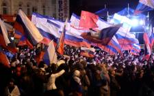 FILE: Pro-Russian Crimeans wave Russian flags as they gather to celebrate in Simferopol's Lenin Square in March after exit polls showed that about 93 percent of voters in Ukraine's Crimea region supported union with Russia. Picture: AFP.