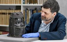 "A handout picture taken on 17 March 2021 at the University of Aberdeen shows Neil Curtis, Head of Museums and Special Collections, posing by a bronze sculpture depicting an ""Oba"" (king) of Benin acquired by the University at auction in 1957. Picture: Kalyan VEERA/University of Aberdeen/AFP"