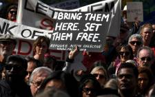 Protesters hold up placards in Melbourne on 1 September 2019, during a rally in support of a Tamil refugee family of four. Picture: AFP