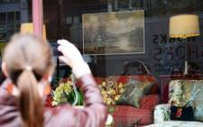 People look at a painting by British artist Banksy on display in a window at Housing Works Gramercy thrift shop on October 30, 2013.Picture: AFP