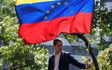 Venezuelan opposition leader and self-proclaimed acting president Juan Guaido is pictured under a national flag during a gathering with supporters after members of the Bolivarian National Guard joined his campaign to oust President Nicolas Maduro, in Caracas on 30 April 2019. Picture: AFP