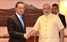 Chinese Foreign Minister Wang Yi (L) and Indian Prime Minister Narendra Modi (R) shake hands during a meeting in New Delhi. Picture: AFP.