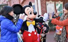 Disney character Mickey Mouse (C) exchange greetings with guests at Tokyo Disneyland in Urayasu, suburban Tokyo on 1 Janury 2014. Picture: AFP