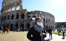 A tourist wearing a protective respiratory mask walks outside the Coliseum in downtown Rome on 28 February 2020 amid fears of Covid-19 epidemic. Picture: AFP