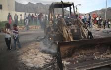 Hangberg community members stand around a burnt construction vehicle used to block roads leading to the community. Photo: Bertram Malgas/EWN