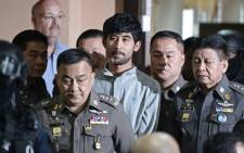 A foreign suspect in the 17 August Erawan shrine bombing, identified by the ruling junta as Yusufu Mieraili (3rd R), is escorted by policemen as he arrives to be questioned by police officers at Bangkoks Metropolitan Police Station on 7 September, 2015. Picture: AFP.