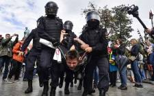 Riot police officers detain a participant of an unsanctioned rally urging fair elections at Moscow's Pushkinskaya Square on 3 August 2019. Picture: AFP.