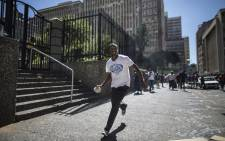 FILE: A man runs with a stone in his hand during a confrontation with foreign nationals in the JHB CBC on 15 April 2015. Picture: AFP.