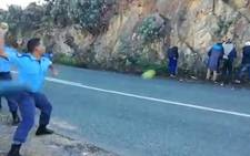 A video screengrab of police officers pelting apples at alleged apple thieves in Theewaterskloof in the Western Cape.