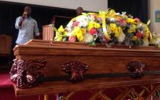Bouquets of flowers draped over the casket with a picture of Kela when he graduated from the University of Johannesburg. Picture: Mia Lindeque/EWN.