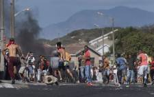 People run away as a South African Police Services armoured vehicle (not visible) approaches them during clashes with residents of Tafelsig, an impoverished suburb in Mitchells Plain, near Cape Town, on 14 April 2020, after some people in the community did not receive food parcels which were being handed out as part of the support for this community during the nation wide lockdown to curb the spread of the coronavirus. Picture: AFP