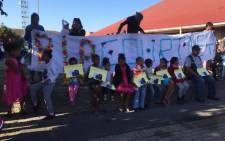 Children hold pictures of three-year-old Courtney Pieters outside a hall where mourners gathered to bid the little girl farewell. Picture: Monique Mortlock/EWN.