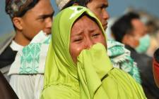A woman cries as people look at the damages after an earthquake and a tsunami hit Palu, on Sulawesi island on 29 September 2018. Picture: AFP