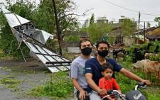 A family rides past damaged billboard due to the impact of Cyclone Tauktae near Amreli on May 18, 2021. Picture: Punit Paranjpe / AFP.