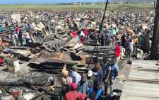Masiphumelele residents sifting through debris following last week's blaze that destroyed around 1,000 homes. Picture: Kevin Brandt/EWN.