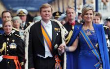 King Willem-Alexander of the Netherlands leaves with his wife Queen Maxima at the Nieuwe Kerk in Amsterdam on April 30, 2013 following his investiture.