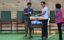 Thai voters drop their ballots at a local polling station during the constitutional referendum in Bangkok on August 7, 2016. Picture: AFP