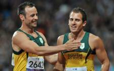 FILE: Oscar Pistorius congratulates Arnu Fourie on winning bronze in the 100m T44 final in the Paralympics. Picture: Sapa.