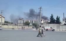 Afghan men walk on a road as smoke rises from the site of an attack in Kabul on 1 July 2019. Picture: AFP