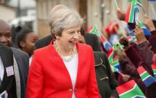 Britain's Prime Minister Theresa May is greeted by schoolchildren waving British and South African flags, during a visit to the ID Mkhize Secondary School in Gugulethu, Cape Town, on 28 August, 2018. Picture: AFP