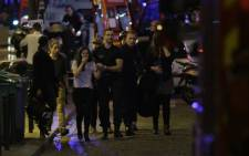 FILE: People are evacuated following an attack at the Bataclan concert venue in Paris, on November 13, 2015. At least 18 people were killed in multiple attacks in Paris Friday, including one near the Stade de France sports stadium.  Picture: AFP