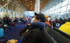 FILE: Passengers wearing protective facemasks amid concerns of the COVID-19 coronavirus outbreak wait to board their plane at Kuala Lumpur International Airport in Sepang on 19 February 2020. Picture: AFP
