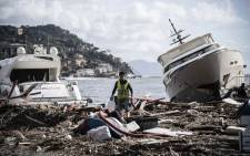 A man walks through garbage between two yachts after a storm hit the harbour and destroyed a part of the dam on 30 October 2018 in Rapallo, near Genoa, Italy. Picture: AFP.