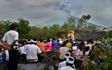 Balinese Hindus take part in a ceremony, where they pray near Mount Agung in hope of preventing a volcanic eruption, in Muntig village of the Kubu sub-district in Karangasem Regency on Indonesia's resort island of Bali on 26 November, 2017. Picture: AFP.