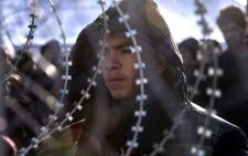 Afghan migrants who have no permission to cross the border between Greece and Macedonia, stay behind a fence, near Gevgelija. Picture: EPA/Georgi Licovski.