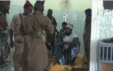 A screengrab from a Boko Haram video shows the movement's leader, Abubakar Shekau (sitting), just before preaching to locals in an unidentified town. Picture: AFP.