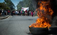 A tyre burns as the UCT FeesMustFall protestors march to university residences. Picture: Anthony Molyneaux/EWN