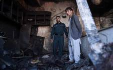 An Afghan policeman and a local resident inspect a burnt shop at the site of a car bomb attack in western Kabul on 24 July 2017. Picture: AFP.