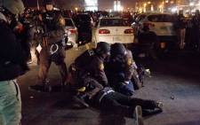 Police make an arrest as protests engulf Ferguson on 26 November, 2014 in Ferguson, Missouri. Over 2,000 Missouri national guardsmen are being deployed a day after demonstrators caused extensive damage in Ferguson and surrounding areas. Picture: AFP.