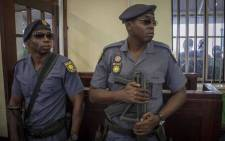 Tactical Response Team police officers, with automatic R5 assault rifles, stand guard at Brits Magistrates court during the case against six murder accused linked to alleged hits on the Platinum belt appeared for the bail hearing. Picture: Thomas Holder/EWN.