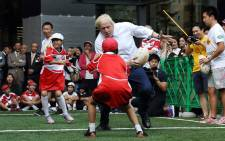 London Mayor Boris Johnson (C) plays rugby with Japanese elementary school children in Tokyo on October 15, 2015 during a promotional event for the 2019 Rugby World Cup which will be held in Japan. Picture: AFP