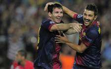 Barcelona's Argentinian forward Lionel Messi (L) is congratuled by his teammate Barcelona's forward David Villa (R) after scoring during the UEFA Champions League football match FC Barcelona against FC Spartak Moscou at the Camp Nou stadium in Barcelona on 19 September, 2012. Picture: AFP.