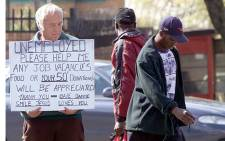 FILE: A white South African begs for money in 2000, while two black men walk by on a street in Johannesburg. Picture: AFP.