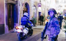 A police officer on a motorbike and a French soldier stands guard after a shooting near the Christmas market in Strasbourg, eastern France, on 11 December 2018. Picture: AFP