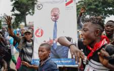 Supporters of Democratic Republic of Congo opposition leader Martin Fayulu hold a placard depecting him, as they march and chant slogans in the streets of the popular Ndjili district of Kinshasa on 19 December 2018 ahead of a campaign rally. Picture: AFP