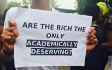 FILE: A student holds a placard at a protest against Wits University's proposed tuition fees increase on 14 October, 2015. Picture: @Zoe_Ngwenyurr via Twitter.