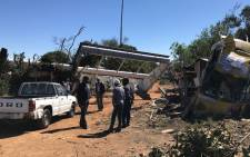 Zandspruit residents begin clean up operations near a fallen billboard a day after a severe thunderstorm on 9 October 2017. Picture: Christa Eybers/EWN