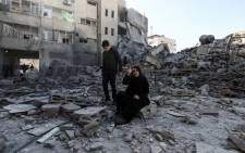 A picture was taken on 26 March 2019, shows a Palestinian woman sitting next to the rubble of a building in Gaza City after Israeli air strikes hit dozens of sites across the Strip overnight in response to rocket fire from the Palestinian enclave. Picture: AFP