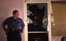 Police guard a strip mall along West Florrisant Street after a store was looted during a demonstration to mark the one-year anniversary of the shooting of Michael Brown on 9 August, 2015 in Ferguson, Missouri. Picture: AFP