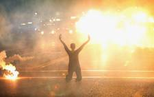 FILE: Tear gas reigns down on a woman kneeling in the street with her hands in the air after a demonstration over the killing of teenager Michael Brown by a Ferguson police officer on August 17, 2014. Picture: AFP.