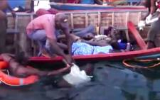 An image grab taken from a video provided by Tanzania's StarTV channel reportedly shows people removing bodies of victims from the water after the ferry MV Nyerere capsized in Lake Victoria, Tanzania, on 21 September 2018. More than 100 people are now known to have died, Tanzanian state media said, citing the country's police chief. Picture: StarTV/AFP