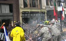 A screen grab from a video shows US soldiers and the general public assisting to rescue survivors of the 2013 Boston Marathon explosions.