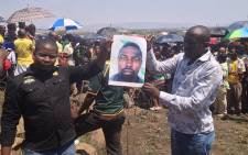 Amplats miners hold up a picture of their comrade who was killed who was killed allegedly by police on 4 October 2012. Picture:Govan Whittles/EWN