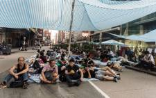 FILE: Commuters eat their breakfast as pro-democracy protesters sleep in the district of Mong Kok in Hong Kong. Picture: AFP.